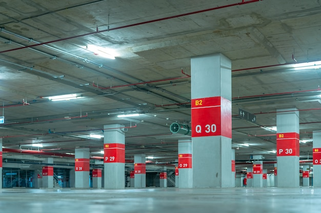 Empty underground car parking lot. underground car parking garage at shopping mall or international airport. indoor parking area. concrete basement floor parking garage.