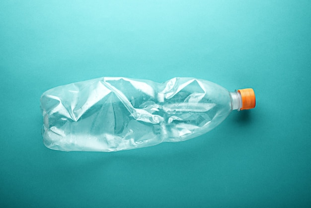 Empty used plastic bottle on neo mint background. environmental pollution concept