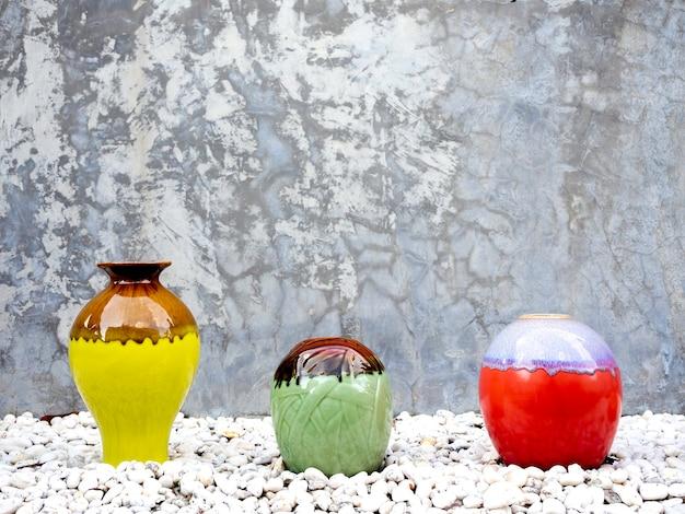 グランジ コンクリート壁の背景に白い砂利の山にカラフルなセラミック花瓶の装飾のさまざまなサイズと形の空の装飾があり、コピー スペースがあります。
