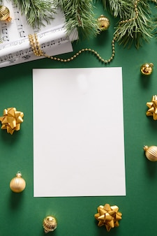 Empty vertical blank for christmas carols and sings decorated golden balls on green