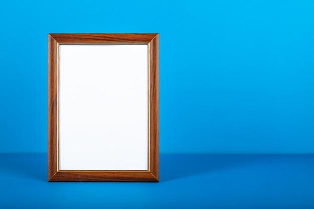 Пустая вертикальная рамка для фотографий на столе. синяя стена.