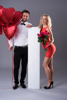 Пустой вертикальный плакат между мужчиной и женщиной