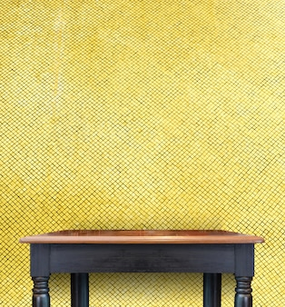 Empty vintage black wooden table top at golden mosaic tiles wall,template mock up for display of your product