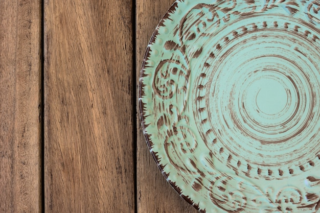 Empty vintage blue plate with ornament on wood table, flat lay, styled photo for menu, marketing