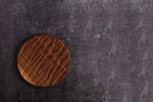 Empty vintage cutting board on dark background, food background concept