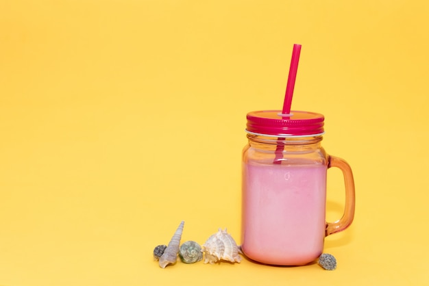 Empty vintage mug with a pink straw and lid on pink background