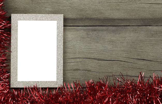 Empty vintage photo frame on wooden floor and red tassels for christmas and new year decorations
