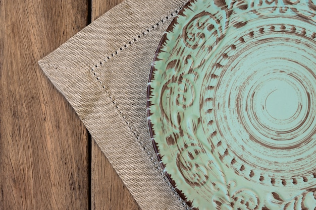 Empty vintage relief plate on linen napkin on plank wood table, top view,  menu template