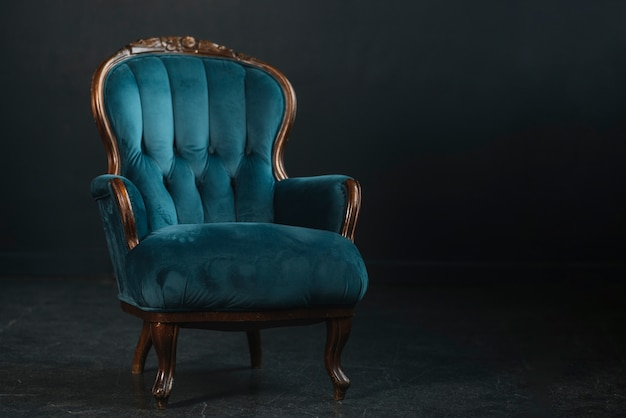 An empty vintage royal blue armchair against black background