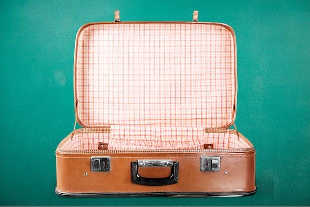 Открытый пустой старинный чемодан изолирован на зеленом фоне