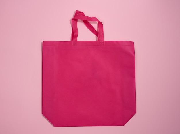 Пустая сумка-тоут из экологически чистой ткани розового цвета из вискозы для брендинга на розовом фоне. прозрачная многоразовая сумка для продуктов, макет. плоская планировка