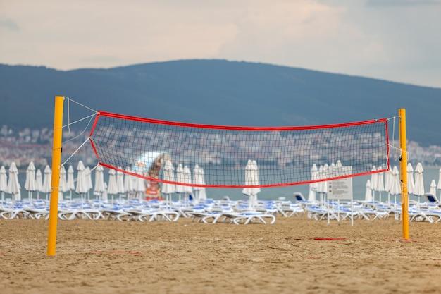 Пустая сеть волейбола на песчаном пляже на береге моря в лете.