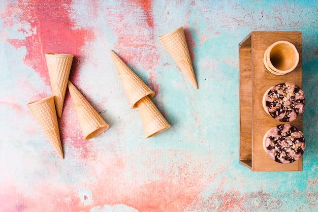 Пустые вафельные рожки и шоколадное мороженое в чашках на разноцветном фоне