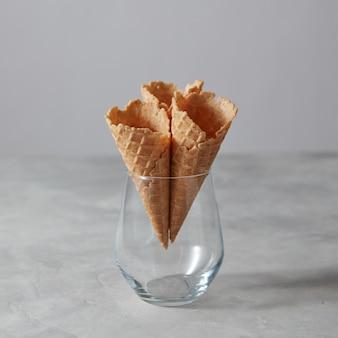 Пустые вафельные рожки для холодного сорбета в стакане на сером фоне с копией пространства. сладкое летнее понятие.