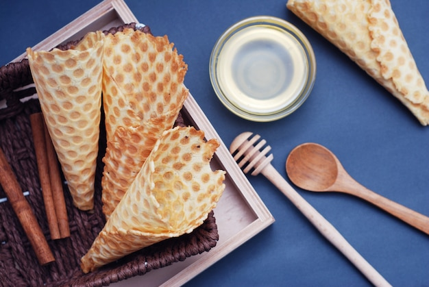 Empty waffle cones homemade dessert and honney. blue background.
