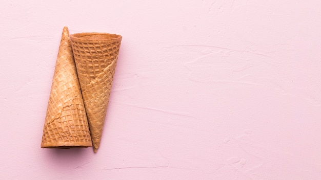 Empty waffle cones on pink background