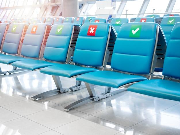 社会的な距離のサインと空の待機椅子