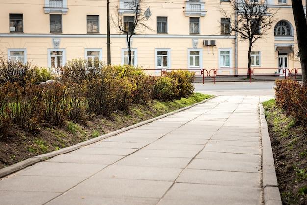 Пустая прогулочная дорожка возле дороги и жилых домов.