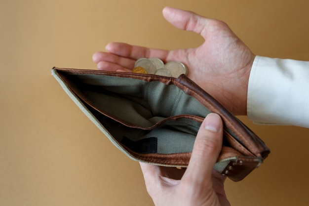 Empty wallet in the hands of a man on a plain background