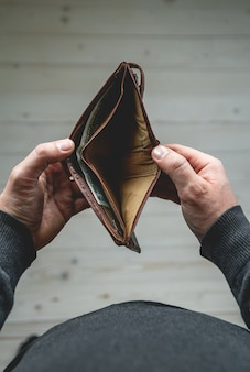 Empty wallet in the hands of a young man