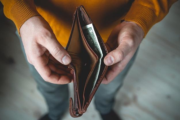 Пустой кошелек в руках молодого человека