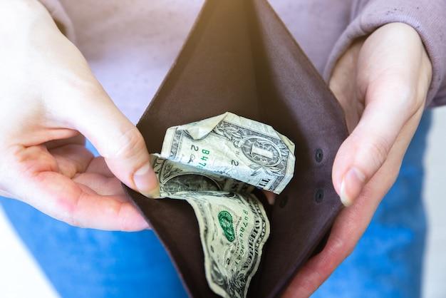 1달러만 있는 빈 지갑. 지갑에 돈이 없습니다. 경제 위기, 빈곤, 실업 개념. 격리 중 코로나바이러스 사람들 격리의 결과. 인플레이션율. 가격 상승.