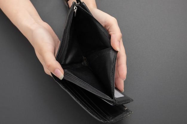 Пустой кошелек без денег в женских руках