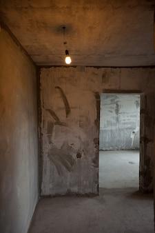 빈 벽 콘크리트 방 인테리어입니다. 전구 하나. 새 방
