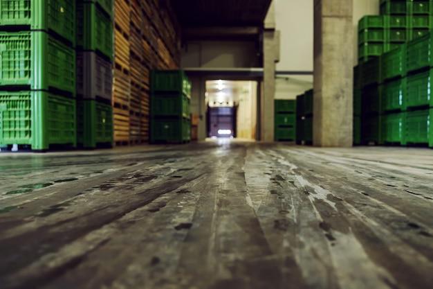 Пустые складские помещения с большим количеством поддонов, аккуратно сложенных на заводе.