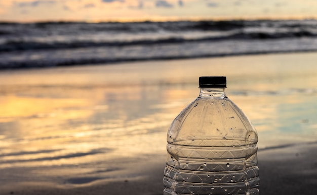 An empty water bottle on a sea beach near the ocean in the golden hour close up