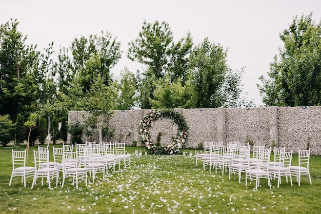 Empty wedding ceremony aisle with chairs in rows and a flower arch
