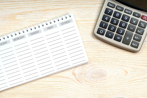 Empty week planner with calculator on office table, work place concept