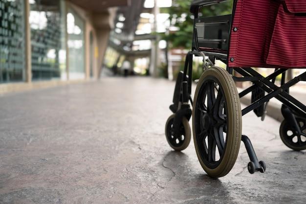 病院の廊下にある空の車椅子。障害者支援のための病院内の医療機器。