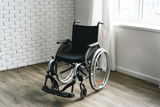 Empty wheelchair in the hospital room near the window