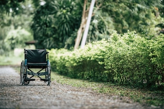 Empty wheelchair parked in park, Health care concept.