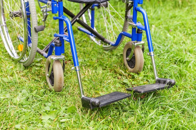 Empty wheelchair standing on grass in hospital park invalid chair for disabled people parked outdoor in nature