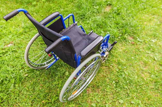 Empty wheelchair standing on grass in hospital park waiting for patient services