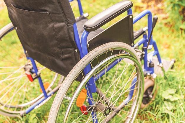 환자 서비스를 기다리는 병원 공원에서 잔디에 서있는 빈 휠체어 프리미엄 사진