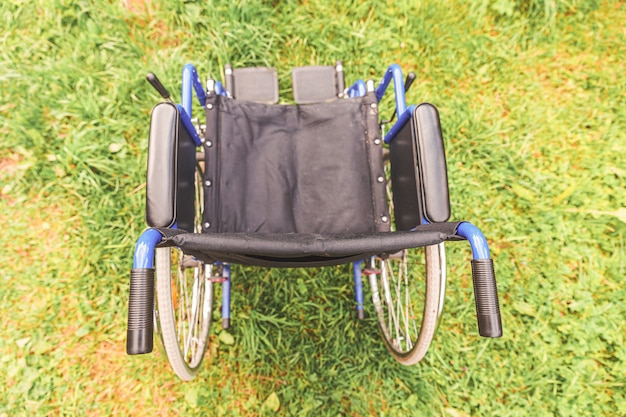 환자 서비스를 기다리는 병원 공원에서 잔디에 서있는 빈 휠체어