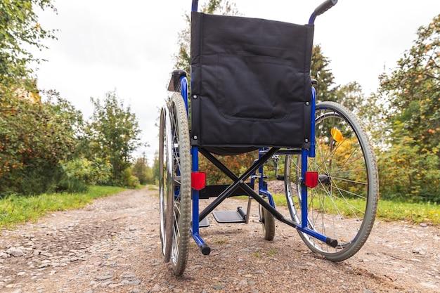 환자 서비스를 기다리는 도로에 서 있는 빈 휠체어. 자연에 야외에 주차된 장애인을 위한 잘못된 의자입니다. 핸디캡 액세스 가능한 기호입니다. 건강 관리 의료 개념입니다.