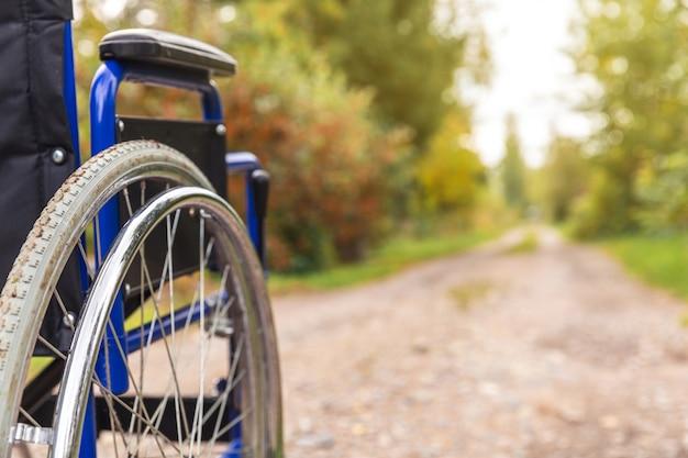 患者サービスを待っている道路に立っている空の車椅子。自然の中で屋外に駐車した障害者用の無効な椅子。ハンディキャップ対応のシンボル。ヘルスケア医療の概念。