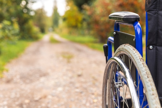Empty wheelchair standing on road waiting for patient services. invalid chair for disabled people parked outdoor in nature. handicap accessible symbol. health care medical concept.