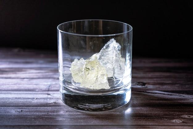 氷の大きな塊と空のウイスキーグラスは、黒い背景のテーブルの上にあります。