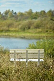 湖の近くの空の白いベンチ