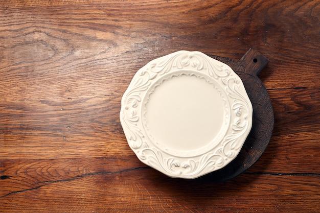 Опорожните белую пустую плиту на деревянной предпосылке с космосом экземпляра. вид сверху.