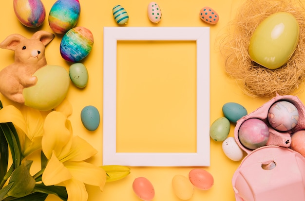 Empty white border frame decorated with easter eggs; lily flower and nest on yellow background