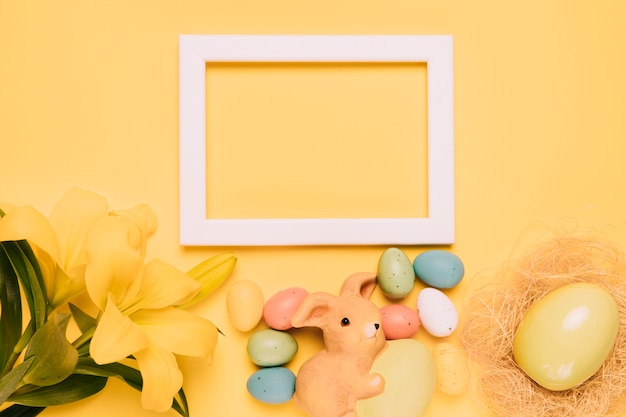 An empty white border frame decorated with lily flowers; rabbit figurine and easter eggs on yellow background
