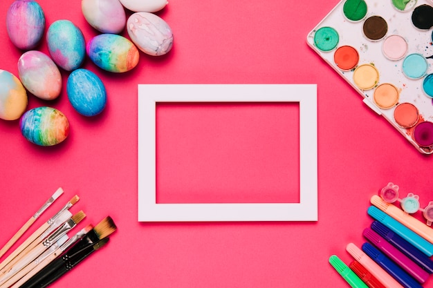An empty white border frame with easter eggs; paint brushes; felt tip pens and water color paint box on pink background