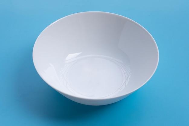 파란색 표면에 빈 흰색 그릇입니다.