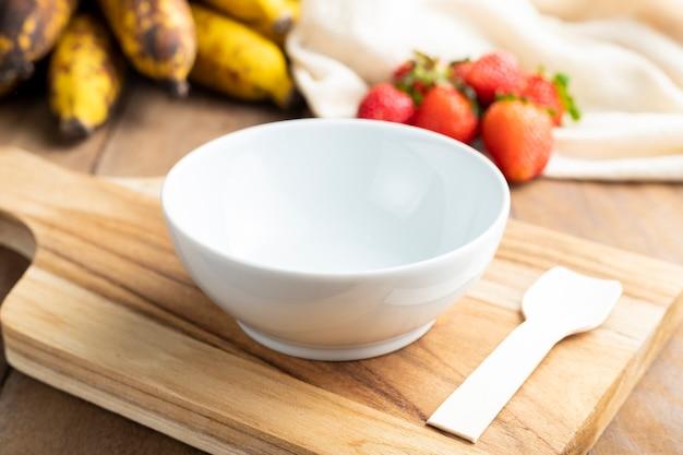 木製のテーブルの上の果物と空の白いボウル